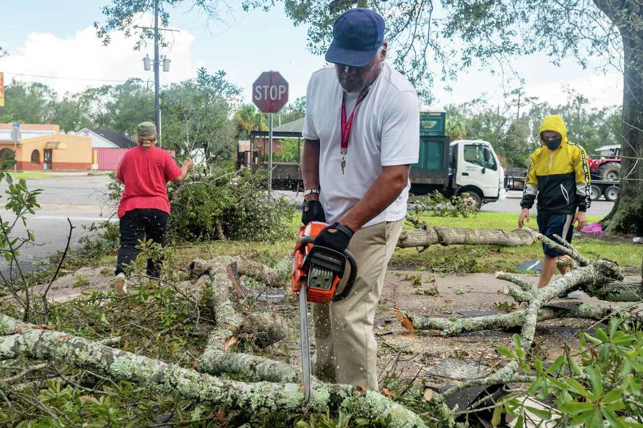 Gilbert Sudillo uses a chain saw to chop branches from a fallen tree at the Ramirez home at 16th and Chapman in Orange. On Friday, the work of recovering from Hurricane Laura continued for many folks, some of whom had evacuated to avoid the storm. Photo made on August 28, 2020. Fran Ruchalski/The Enterprise Photo: Fran Ruchalski, The Enterprise / The Enterprise / © 2020 The Beaumont Enterprise