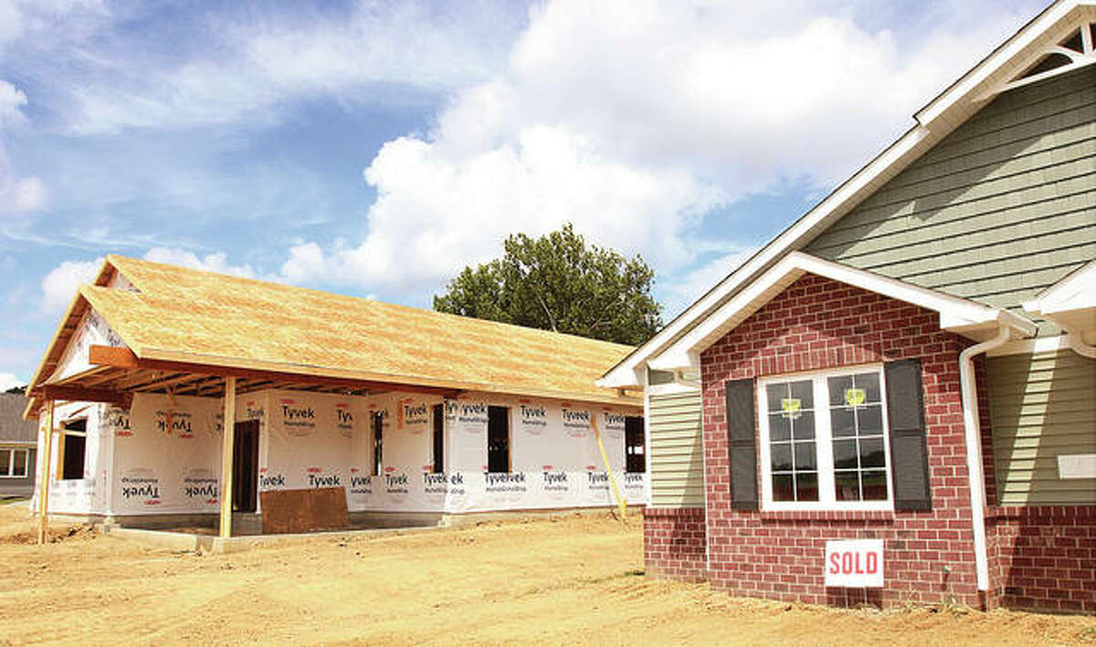 """While one home is now under construction at """"The Cottages at Davis Pond"""" in Godfrey, another, right, has already been sold. Five homes are planned in the development."""