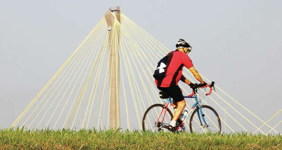 A bicyclist uses a Madison County Transit bike trail atop the levee in Alton. The trail is one of nine interconnected trails in Madison County, extending 137 miles in all.