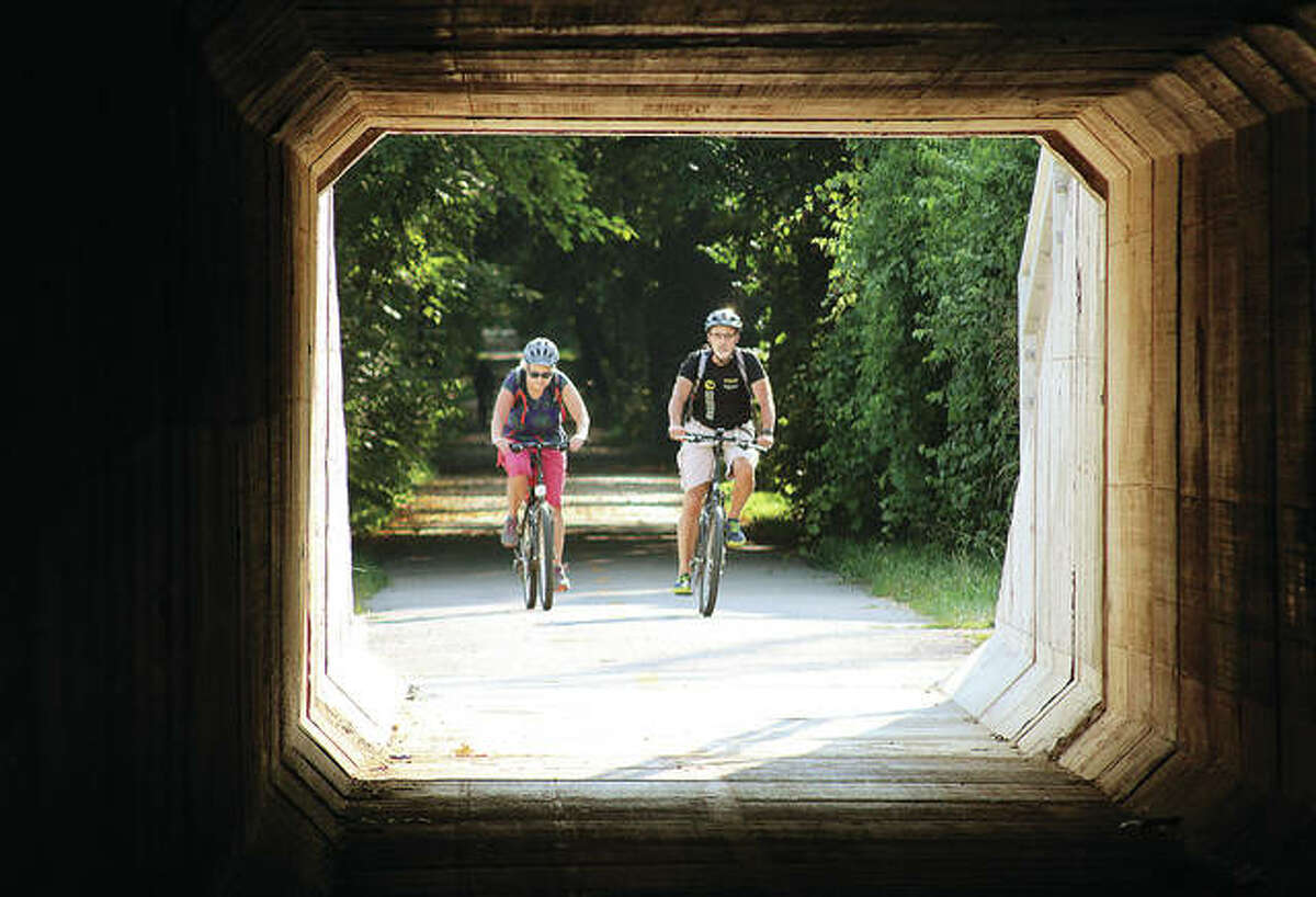 Two bicyclists head into the tunnel of the Goshen Trail as it runs underneath Illinois 157 in Edwardsville. The Goshen Trail, at nearly 20 miles long, is one of the longest in the Madison County Transit system of bikeways and trails.