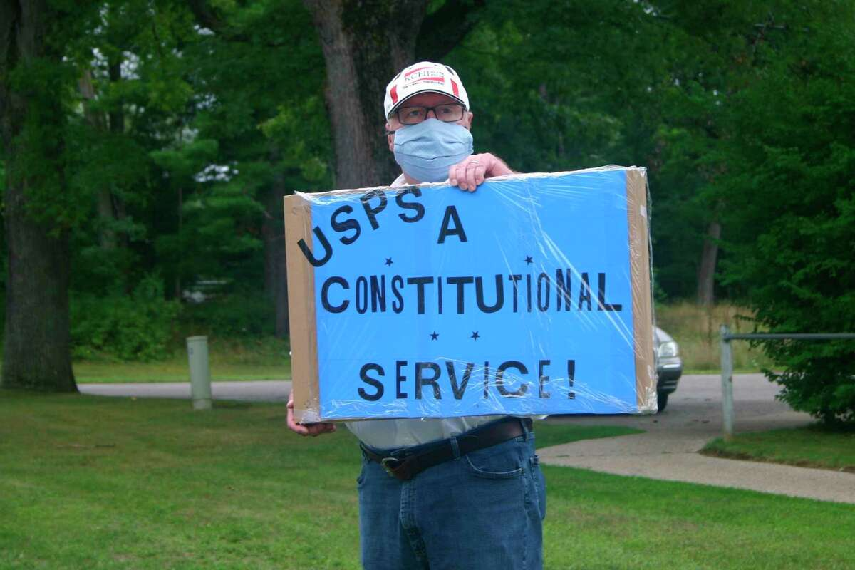 As residents came and went at the post office in Baldwin, others gathered with signs to protest recent changes to the US Postal Service and possible shut downs of rural post offices on Saturday, Aug. 29. (Pioneer photo/Cathie Crew)