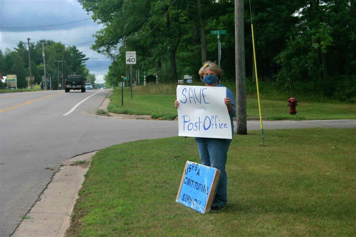 """Signs saying, """"Save our Post Office"""" and """"The USPS is NOT a corporation"""" were on display in Baldwin on Saturday, Aug. 29, as local residents protested recent changes to the USPS. (Pioneer photo/Cathie Crew)"""