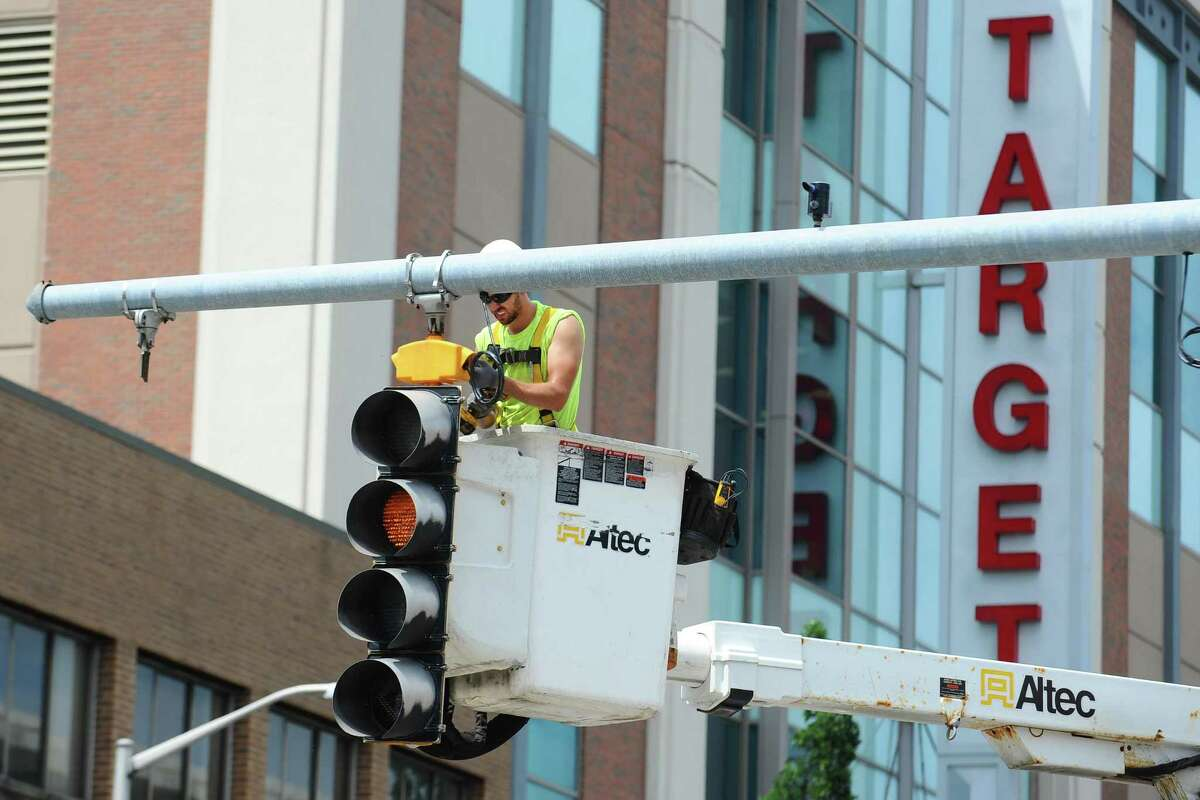 An Altec employee works on fixing a traffic light at the corner of Summer St. and Broad St. in downtown Stamford on Friday, July 15, 2016.