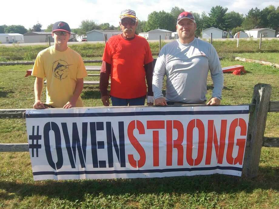 Reed City Sportsman Club president Mike Adrianse stands with Owen Stricker's dad Shane (right) during Saturday's benefit shoot. (Courtesy file)
