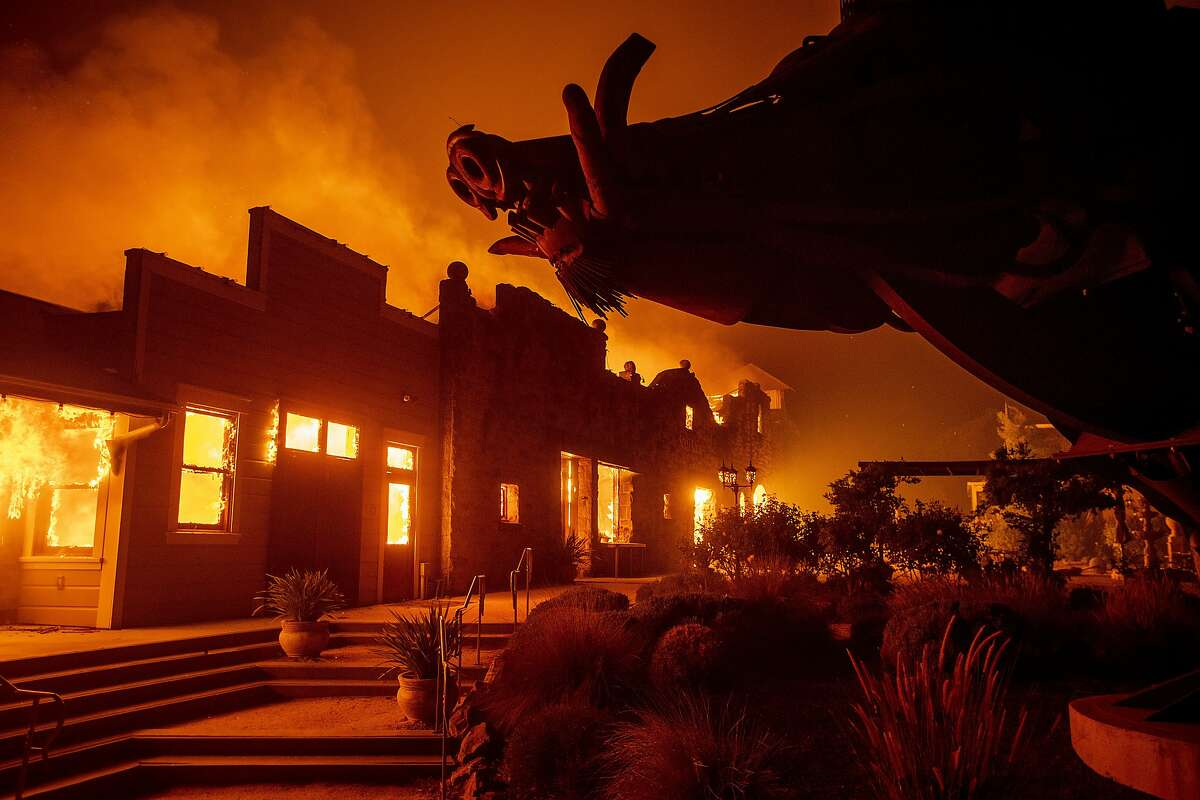 FILE - In this Oct. 27, 2019 file photo, flames from the Kincade Fire consume Soda Rock Winery in Healdsburg, Calif. Wildfire has been cruel to Northern California wine country lately. Major fires during three of the past four years have charred vineyards, burned down a historic winery and sent plumes of smoke above the neatly tended rows of vines that roll across the scenic hills. (AP Photo/Noah Berger, File)