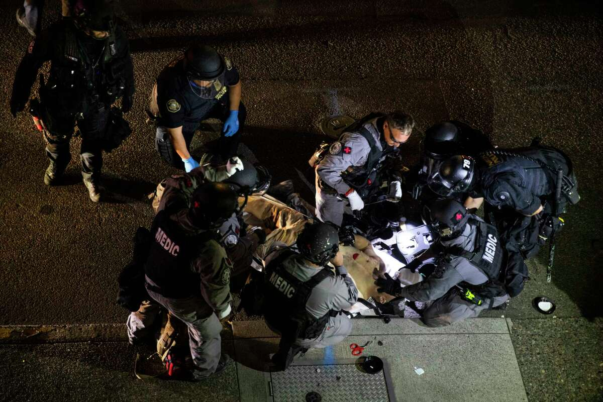 ADDS THE SHOOTING WAS FATAL - A man is treated after being shot Saturday, Aug. 29, 2020, in Portland, Ore. It wasna€™t clear if the fatal shooting late Saturday was linked to fights that broke out as a caravan of about 600 vehicles was confronted by counterdemonstrators in the citya€™s downtown. (AP Photo/Paula Bronstein)