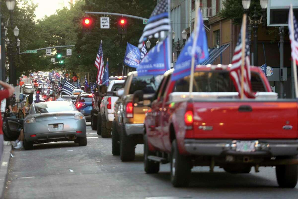A caravan of supporters of President Donald Trump drive in downtown Portland, Ore., Saturday, Aug. 29, 2020. Saturday's rally was the third consecutive weekend that pro-Trump demonstrators converged in and around Portland, leading to clashes with counter protesters. (Dave Killen/The Oregonian via AP)