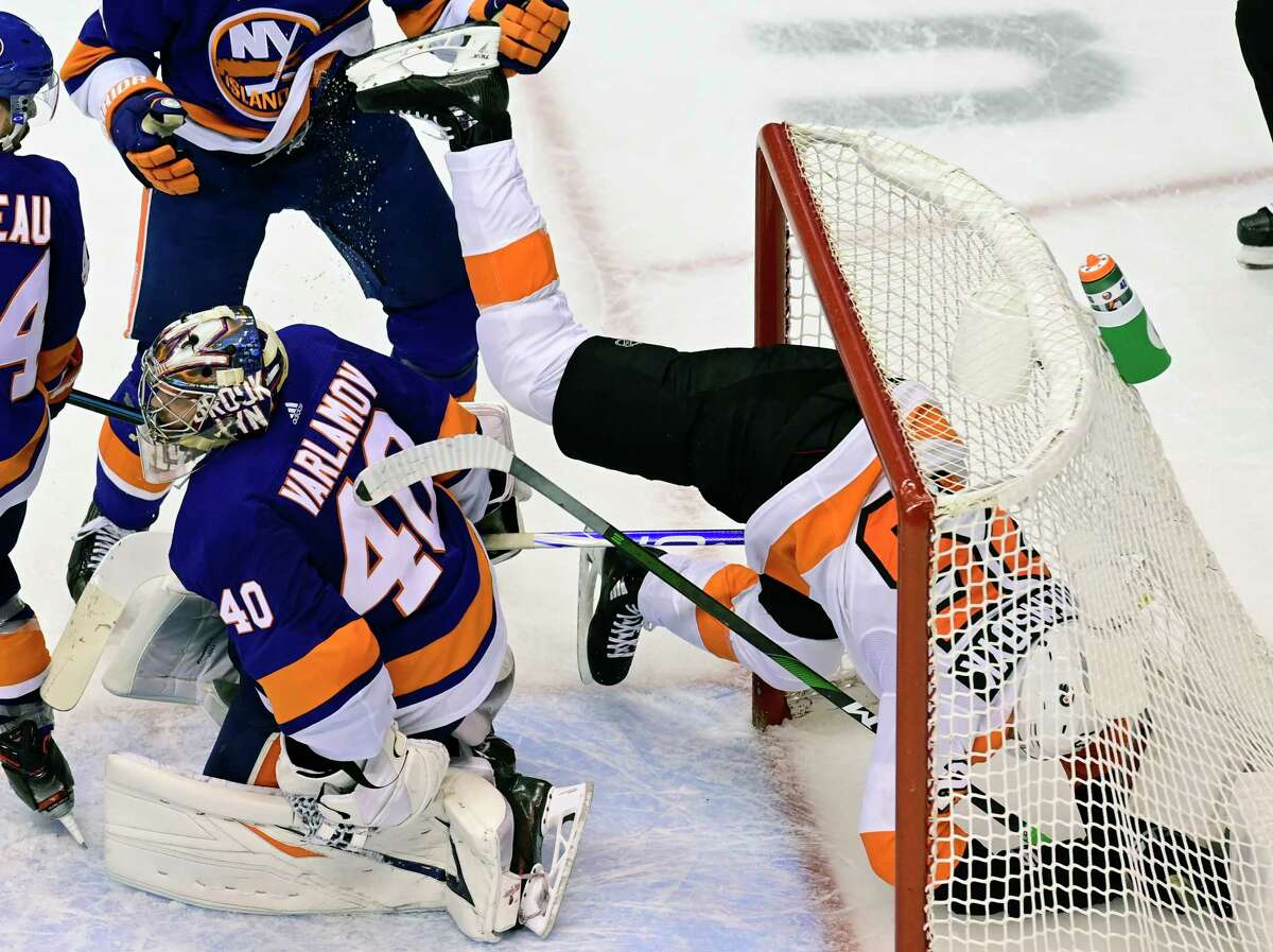 Philadelphia Flyers left wing James van Riemsdyk (25) crashes into the net behind New York Islanders goaltender Semyon Varlamov (40) during third-period NHL Stanley Cup Eastern Conference playoff hockey game action in Toronto, Saturday, Aug. 29, 2020. (Frank Gunn/The Canadian Press via AP)