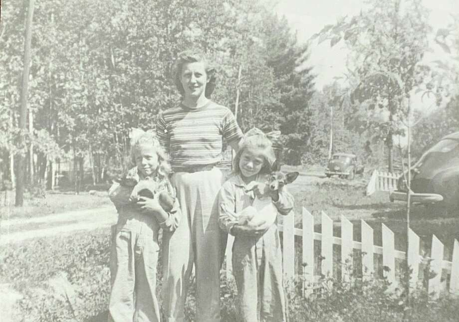 Vicki Goodshaw stands with her mom, Lorraine Goodshaw, and sister, Tammy, at the family conclave on Loebrich Drive at Three Rivers. The puppies in the photo were borrowed and had to be given back. This photo was taken 1944.