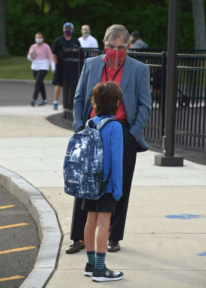 Assistant Principal John Grasso helps a student find their way to their classroom on the first day of the new school year at South Elementary School in New Canaan, Conn, Monday, August 31, 2020. Back on March 11, New Canaan students were sent home and immediately became immersed in distance learning. Sports seasons were canceled. Extracurricular activities were called off or radically changed, those that were held had to be conducted via cyberspace. But that changed on Monday, as for the first time in five-and-a-half months students entered buildings, which were set up differently than they were pre-COVID. Directions are dictated in hallways to prevent crowding, masks are required, and there are physical barriers and efforts to maintain social distancing, including outdoor learning. High school athletes have been given the green light to conditions for the fall season, but whether, or for how longs, games will be played remains unclear, with discussions continuing between the state Department of Health and the Connecticut Interscholastic Athletic Conference.  Photo: H John Voorhees III / Hearst Connecticut Media / The News-Times
