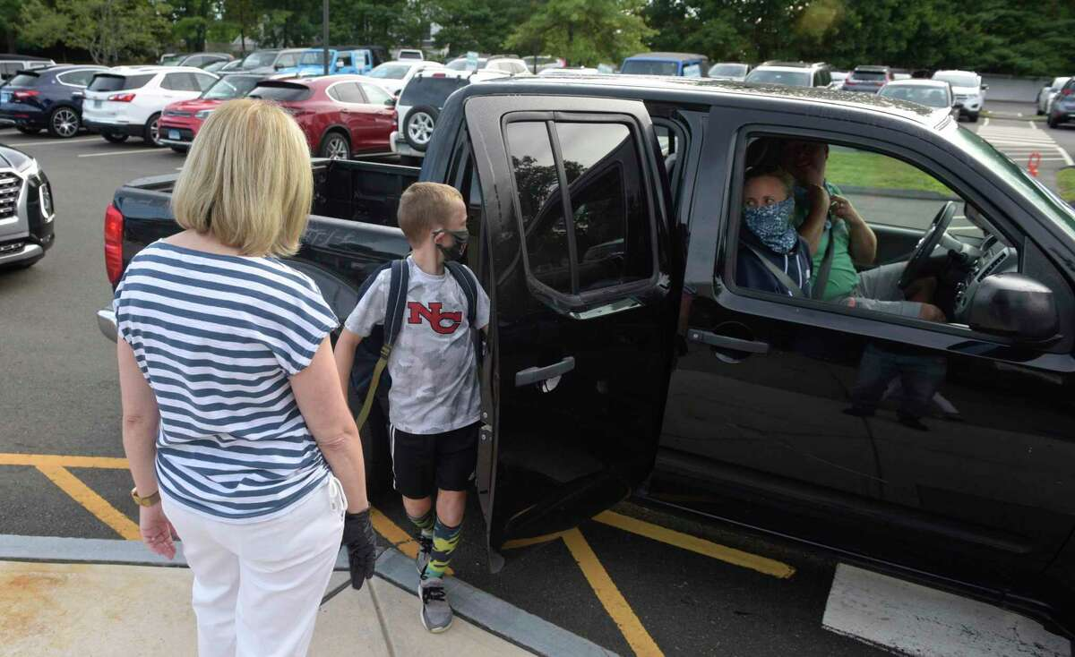 A student is dropped off on the first day of the new school year at South Elementary School in New Canaan, Conn, Monday, August 31, 2020.