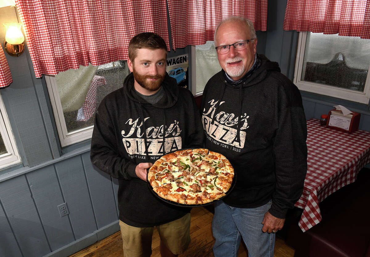 Kay's Pizza owner Tom Lilly, right and his son James stand inside of Kay's Pizza with a pizza on Thursday, Aug. 27, 2020 in Averill Park, N.Y (Lori Van Buren/Times Union)