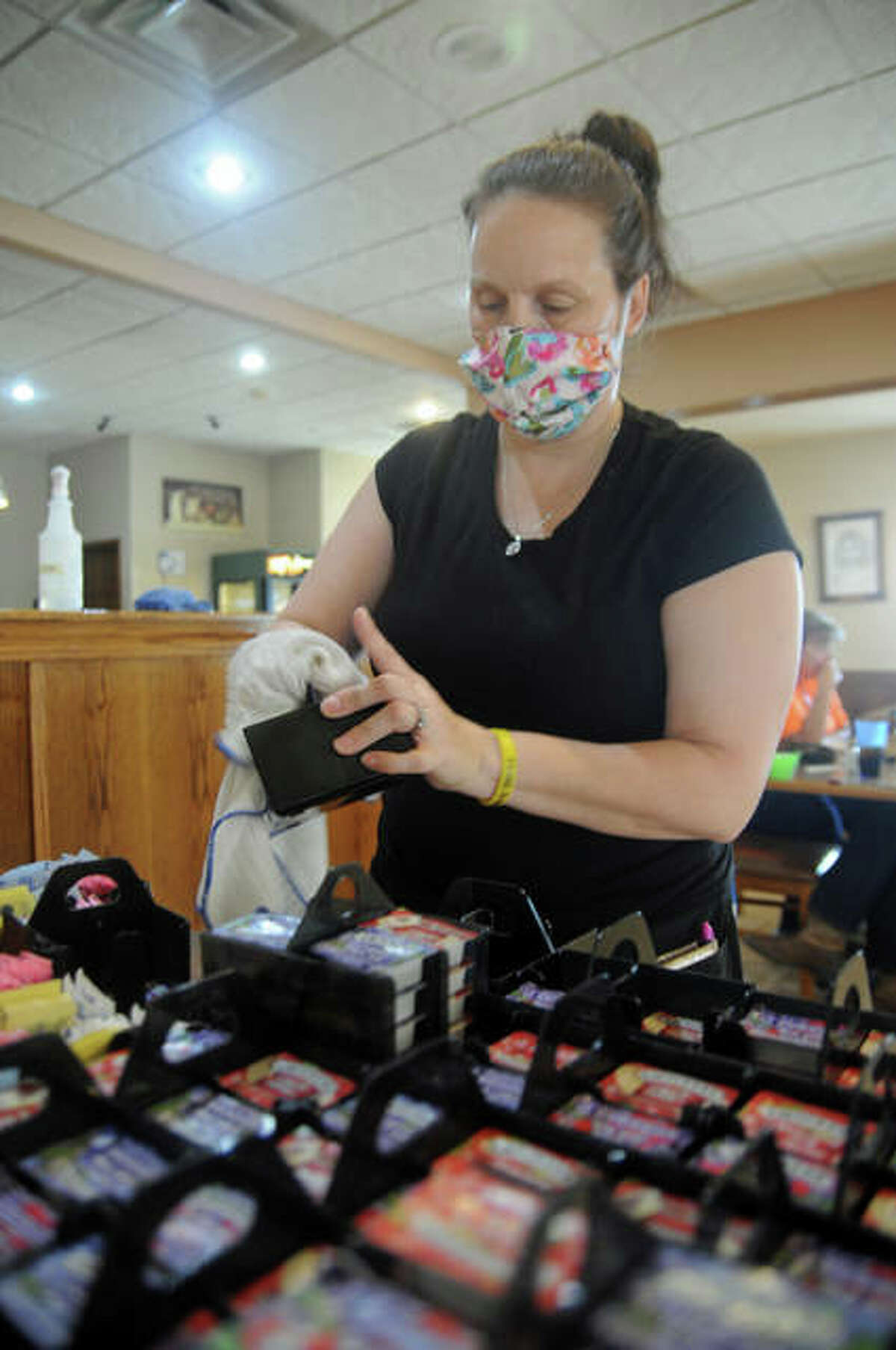 Jeni Nape, a server at the Olive Branch Cafe in Jerseyville, sanitizes condiment holders that were on customers' tables during the noon lunch rush on Saturday. Pandemic concerns have added a lot of time to wait staff's schedules, she said.