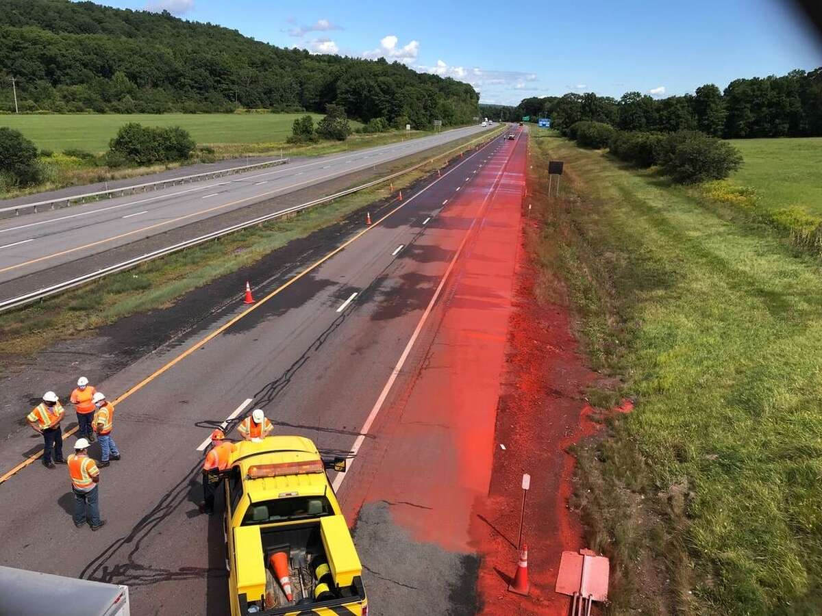 A tractor trailer hauling a cargo of powderediron oxide coated a westbound portion of the Thruway in an orange dust after it hit a bridge abutment that tore a hole in the cargo box, officials said. Crews spent Monday morning cleaning the dust off of the highway.