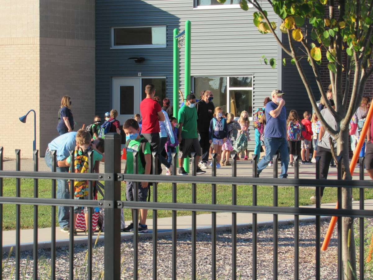 Teachers lead students into Central Park Elementary School on the first day of school on Monday, Aug.31, 2020.