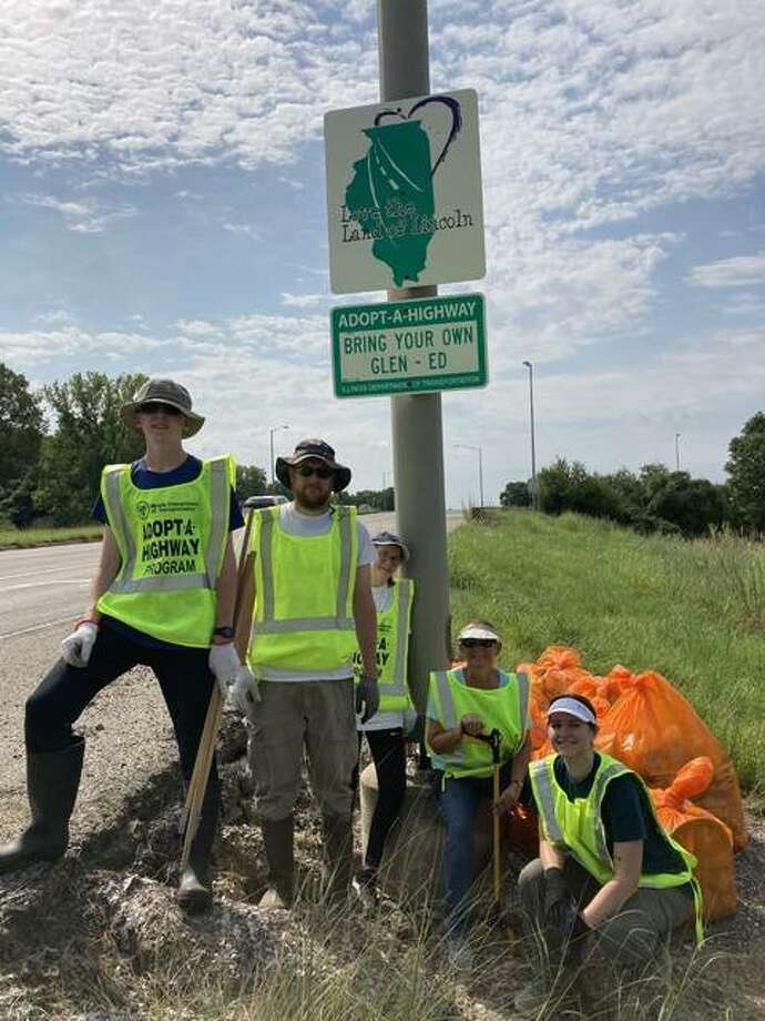 On Saturday, Bring Your Own Glen-Ed members stand under a sign notifying drivers that the stretch of Illinois State Route 157 they are on is maintained by the group. Photo: Courtesy Of Bring Your Own Glen-Ed