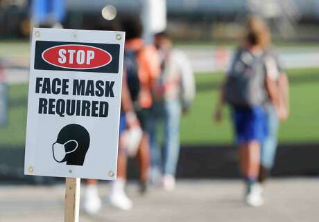A sign tells fans face masks are required for a non-district high school football game between Splendora and Tyler Chapel Hill, Aug. 28 in Tyler.