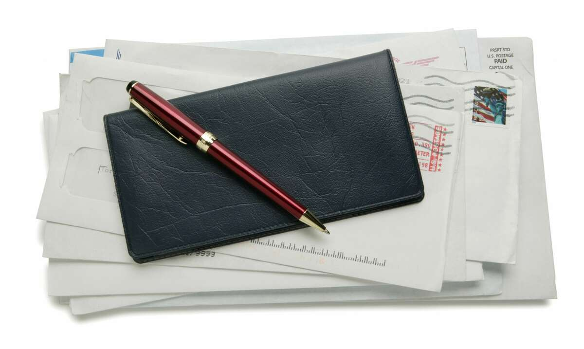 Pen and checkbook sitting on pile of bills