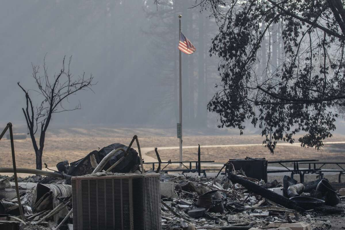 In this Aug. 26, 2020 photo, the American flag still flies over the remains of the Little Basin Campground visitor center in Big Basin Redwood State Park after the park was ravaged by the CZU Complex fire near Boulder Creek, Calif. In heavily damaged areas, crews were working to restore electricity and water so more people could return to their homes.