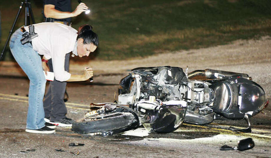 Alton Police Sgt. Emily Henja, head of the Alton Police Department's Traffic Division, gets a closer look at the badly mangled motorcycle Sunday night on which Elvin D. Longstreet, 31, of Alton was riding when he collided with a Nissan Altima, resulting in his death. The accident occured before 8 p.m. Sunday on Washington Avenue at its intersection with Moore Street. According to preliminary reports from the Madison County Coroner's Office, the driver of the Nissan turned into Longstreet's path, causing the collision.