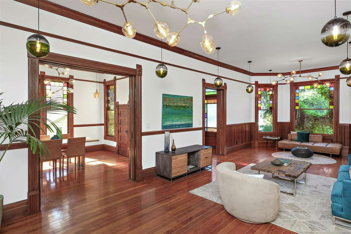A large living room showcasing hard wood floors and accents.