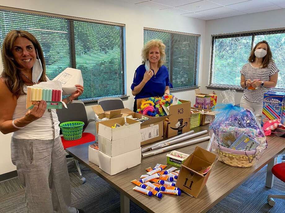 Kim DiMatteo, left, branch manager at DiMatteo Insurance in Shelton, helps create summer beach baskets that the firm delivered to shelters in Norwalk and Stamford. The back-to-school themed baskets were donated by DiMatteo Financial, DiMatteo Insurance and ACBI Insurance, all located in Shelton. DiMatteo is pictured with fellow employees Linda Ayles of Monroe, center, and Jamie Nickerson of New Milford. Photo: DiMatteo Insurance / Contributed Photo / Connecticut Post