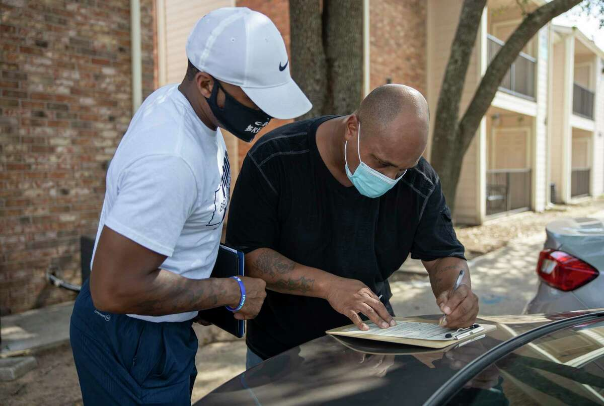 LaDon Johnson, left, assists Jimmie Deveraux III, right, fill out a voter registration form in Conroe, Thursday, July 9, 2020.