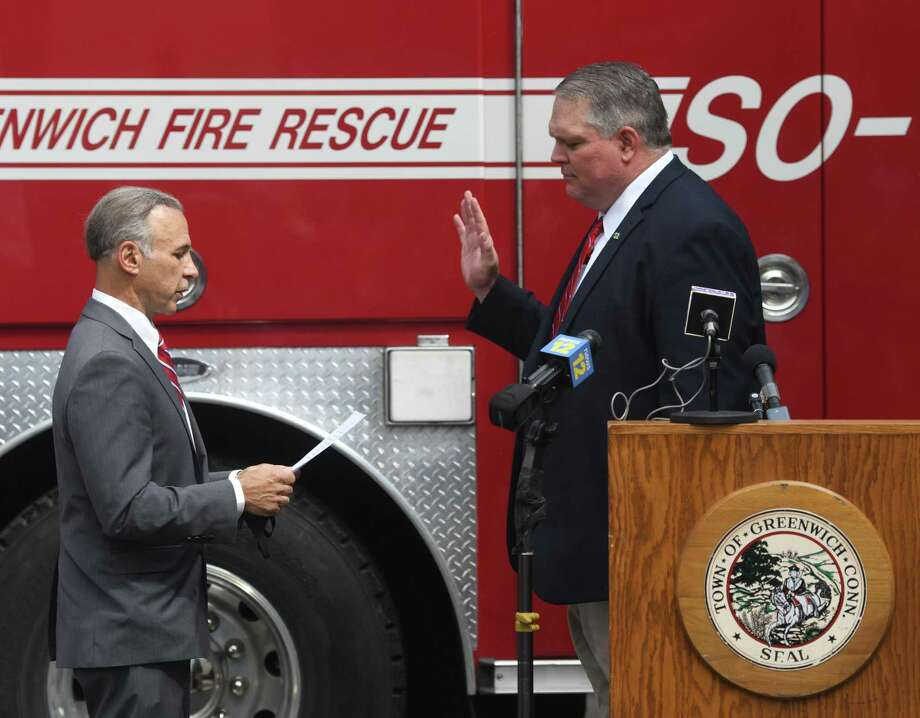 Incoming Fire Chief Joseph McHugh, right, is sworn in by First Selctman and Fire Commissioner Fred Camillo at the Public Safety Complex in Greenwich, Conn. Monday, Aug. 31, 2020. McHugh grew up in Greenwich and spent most of his career with the FDNY. The incoming Fire Chief will succeed Peter Siecienski, who retired in May, and begin his role on Sept. 14. Photo: Tyler Sizemore / Hearst Connecticut Media / Greenwich Time
