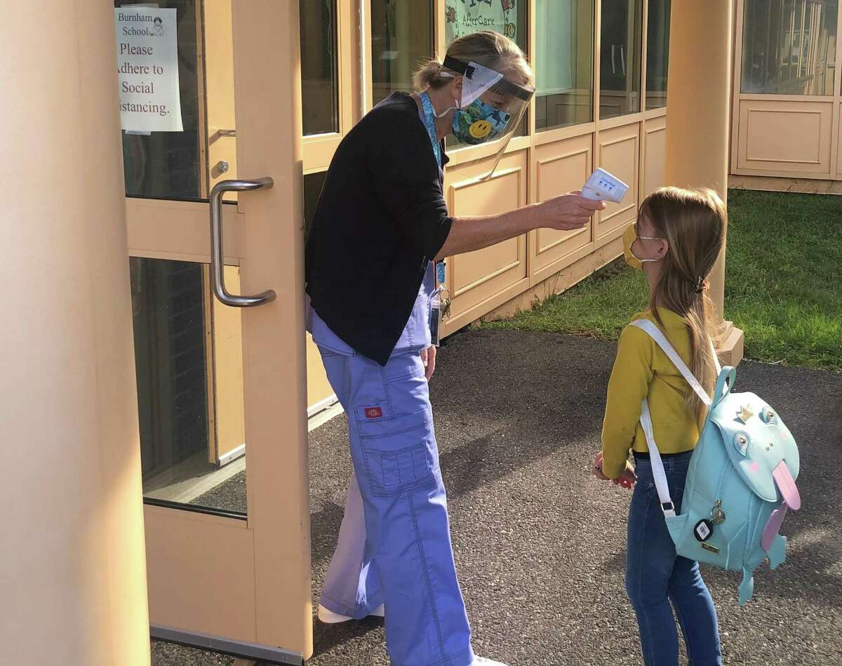 Region 12, which serves the towns of Washington, Bridgewater and Roxbury, opened its school doors Aug. 31, 2020, for the first day of school for the 2020-21 academic year, during the coronavirus pandemic. First-grader Lillian Wilson ha her temperature taken by nurse Lisa McQueen before she enters Burnham School in Bridgewater.