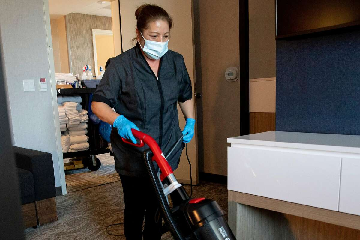 A housekeeper cleans at a Bay Area hotel in August. S.F.'s plans to close hotels for the homeless is on hold.