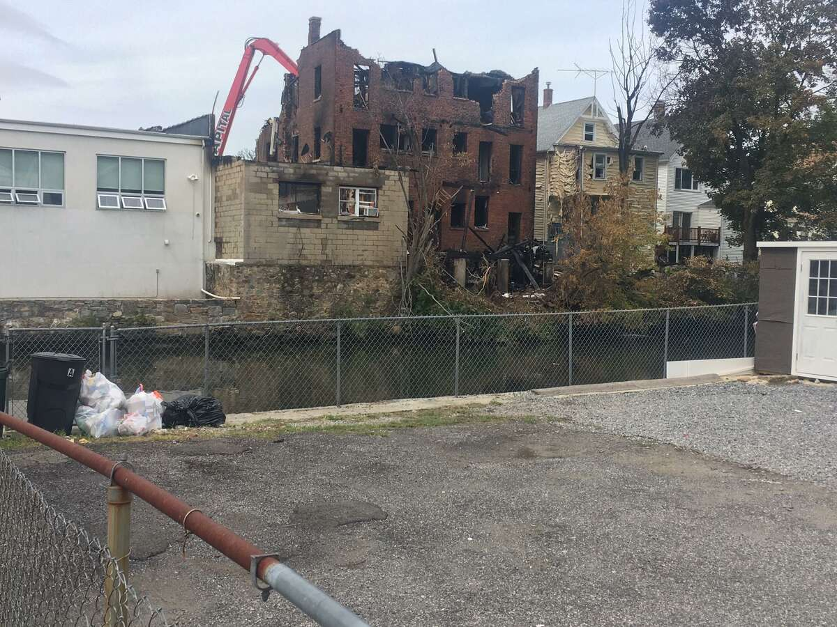 Workers demolished a badly damaged structure in Port Chester, N.Y., just over the Byram River after a major fire. Greenwich firefighters blasted water at the blaze from North Water Street.