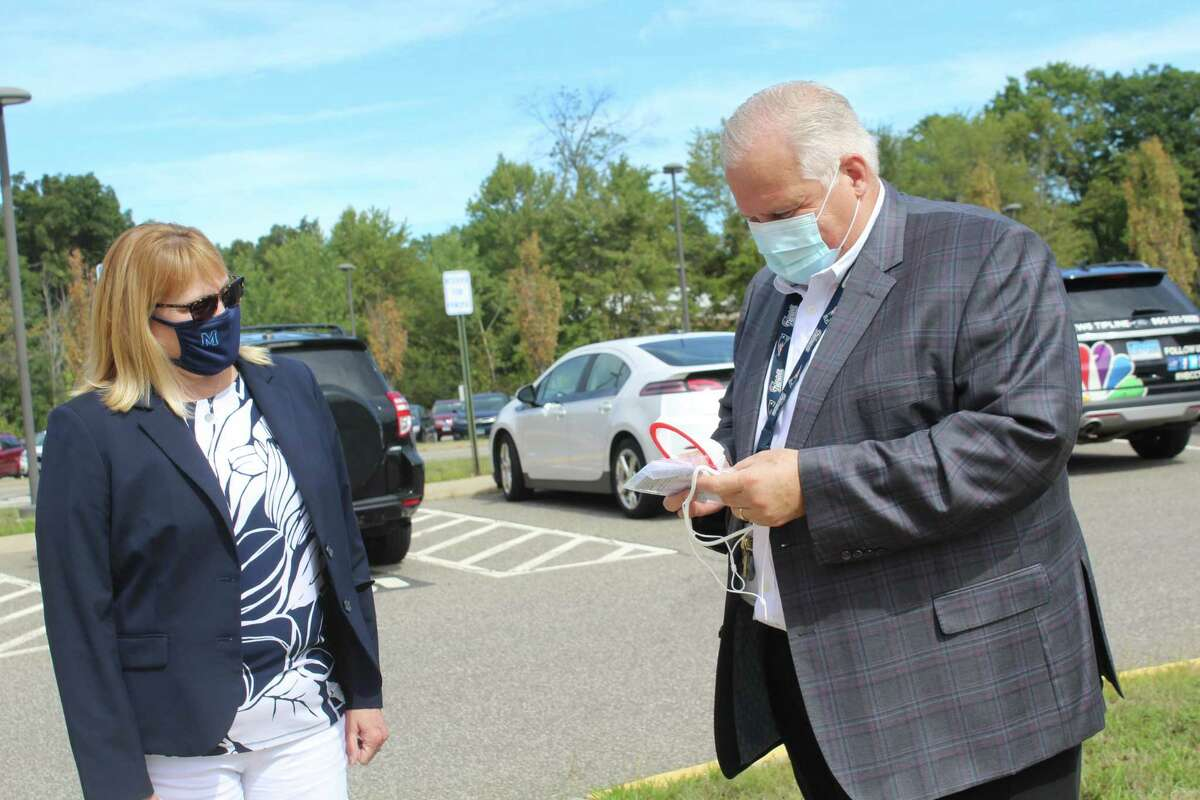 Middletown High School Principal Colleen Weiner, left, watches Chief of School Operations and Communications Marco Gaylord open a Biotech mask.