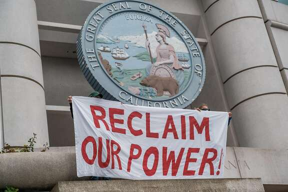 People hold banners as they protest against a PG&E bailout in San Francisco, Calif. on Wednesday, May 20, 2020.