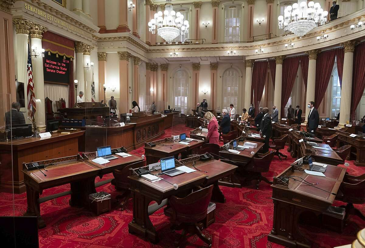 The senate chambers is absent of Republican members during opening prayers at the State Capitol on Thursday, Aug. 27, 2020, in Sacramento, Calif. All but one of the Republicans in the California Senate were barred from the state Capitol on Thursday after they were exposed to the coronavirus, prompting unprecedented changes that will allow them to vote via video conference from their homes as the Legislature rushes to complete its work by Monday's deadline. (Paul Kitagaki Jr./The Sacramento Bee via AP)
