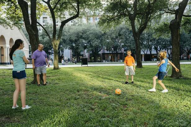 A dad plays with his children in Houston's Galleria area.
