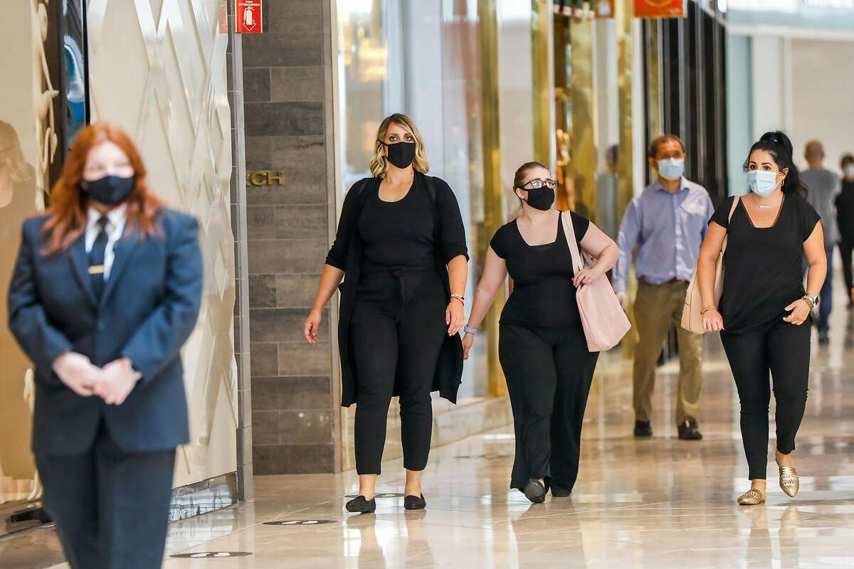 People walk through the Westfield Valley Fair Mall hours after it reopened following the COVID-19 global pandemic in San Jose, California, on Monday, Aug. 31, 2020.