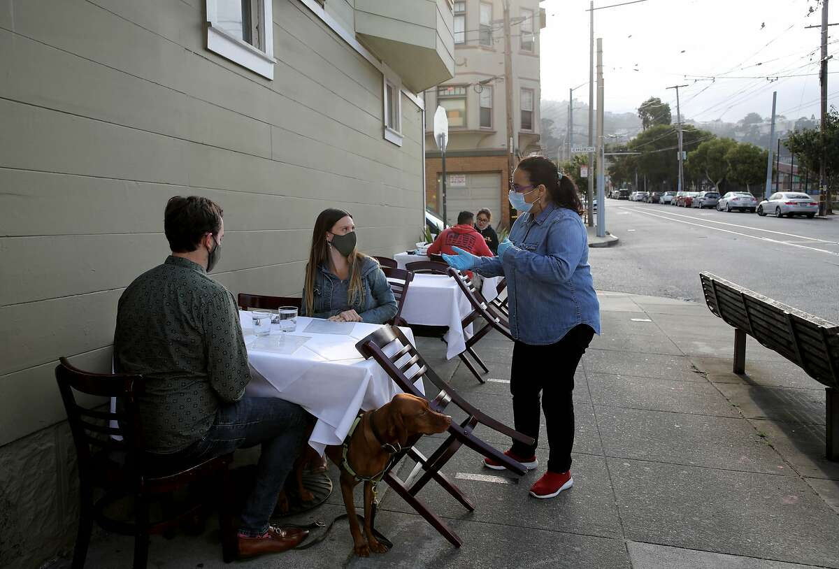 Lorella Degan, co-owner of La Ciccia located at 291 30th Street, converses with diners Mike Ihbe and Leila Wozniak and their dog Goose as they prepare to have a meal at the establishment on Thursday, August 27, 2020, in San Francisco, Calif. La Ciccia is a popular SF restaurant with an outdoor dining space frequented by dinner crowds from its surrounding neighborhood.