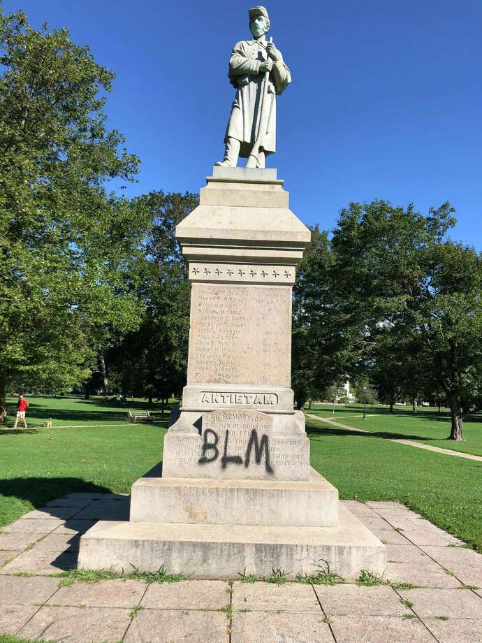 """Guilford Parks & Recreation Department workers began removing this """"Black Lives Matter"""" graffiti found Saturday on the Civil War monument on the Guilford Town Green. But the town will hire an outside contractor after the attempt to remove it was only partially successful. Photo: Contributed Photo"""