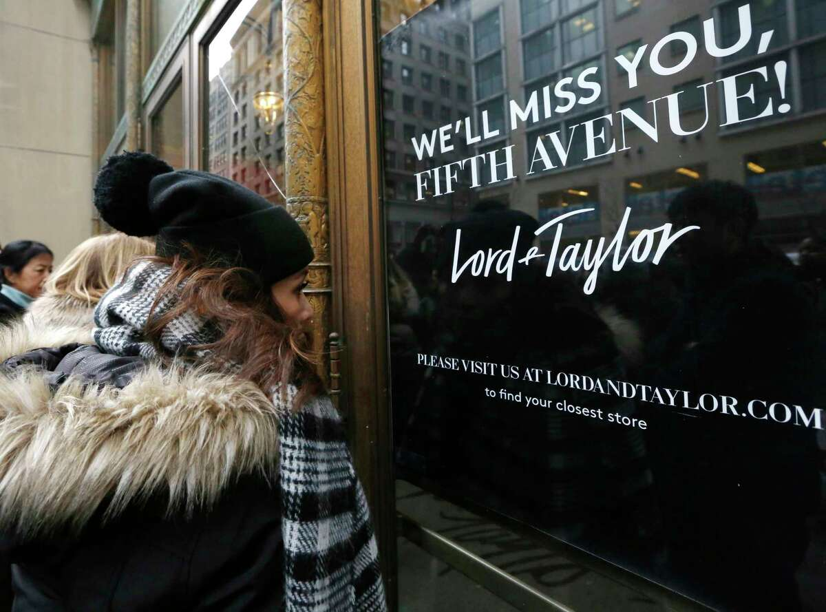 FILE - In this Jan. 2, 2019 file photo, women peer in the front door of Lord & Taylor's flagship Fifth Avenue store which closed for good, in New York. A slew of once-beloved brands from Lord & Taylor to Ann Taylor have filed for Chapter 11 since the pandemic. Many shoppers will see these iconic labels vanish or become mere shadows of themselves as they drastically shrink their businesses or get acquired. But while loyal customers bemoan their loss, the brands themselves have been clearly losing favor for year. (AP Photo/Kathy Willens, File)