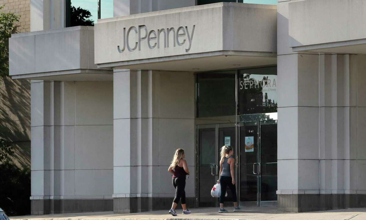 FILE - In this Aug. 14, 2019, file photo two women walk into the JCPenney store in Peabody, Mass. J.C. Penney filed for Chapter 11 in May 2020 and announced plans to permanently close nearly a third of its 846 stores. A slew of once-beloved brands have filed for Chapter 11 since the pandemic. Many shoppers will see these iconic labels vanish or become mere shadows of themselves as they drastically shrink their businesses or get acquired. But while loyal customers bemoan their loss, the brands themselves have been clearly losing favor for year. (AP Photo/Charles Krupa, File)