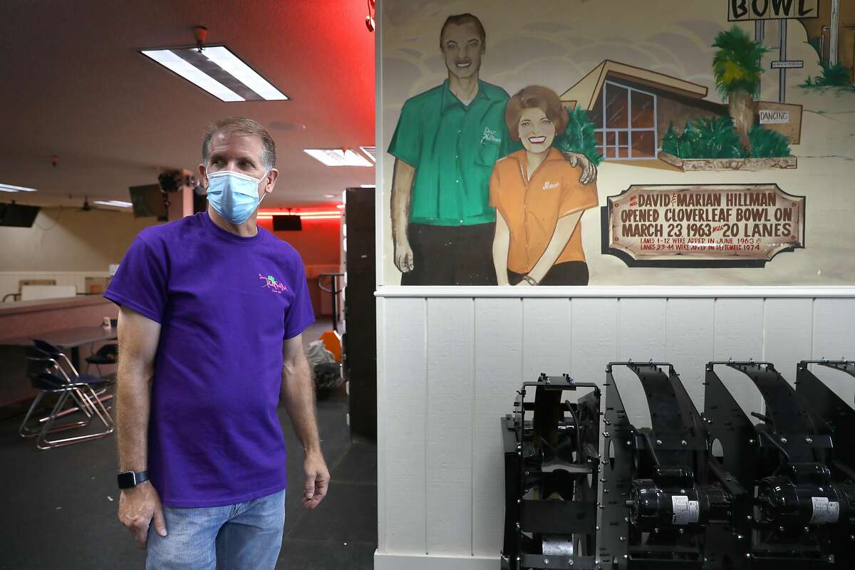 Third generation owner Mike Hillman (left) shows a mural of his grandparents David and Marian Hillman who opened the Cloverleaf Bowl in 1963 seen at the alley on Thursday, Aug. 27, 2020, in Fremont, Calif.