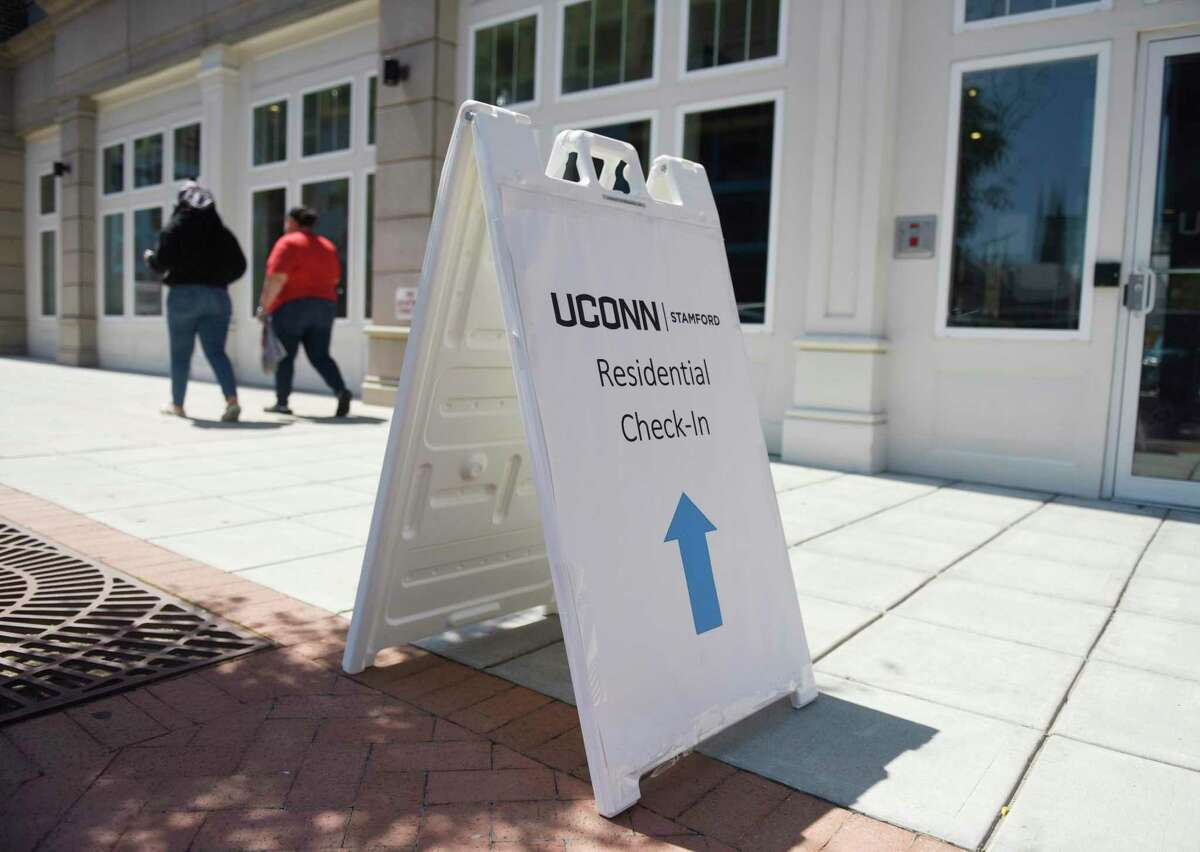 A sign leads to check-in for the student dorms at the UConn Stamford branch in August. Health experts say active screening for COVID-19 is critical in preventing college outbreaks.