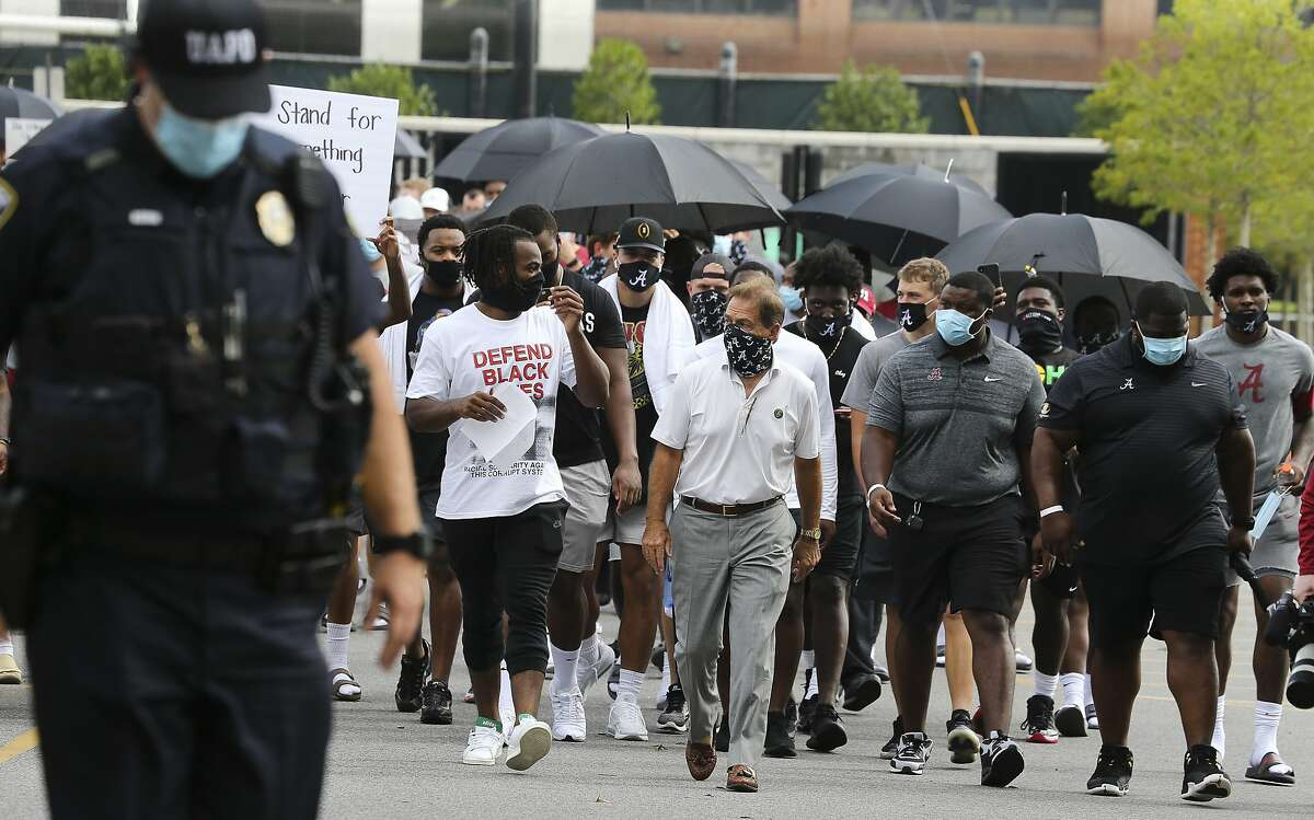 Coach Nick Saban and running back Najee Harris, left, lead the University of Alabama football team and other student athletes Monday, Aug. 31, 2020, in Tuscaloosa, Ala., as they march to Fosters Auditorium, the sight of the famous stand in the Schoolhouse Door to voice their support for social justice. (Gary Cosby Jr./The Tuscaloosa News via AP)