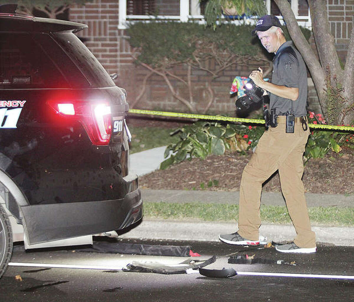 An Alton Police officer walks past debris on Washington Avenue near a police car early Saturday morning where an Alton Police officer was struck by a car fleeing police. On Monday charges were filed against an Alton woman and two men from St. Louis in connection to the incident.