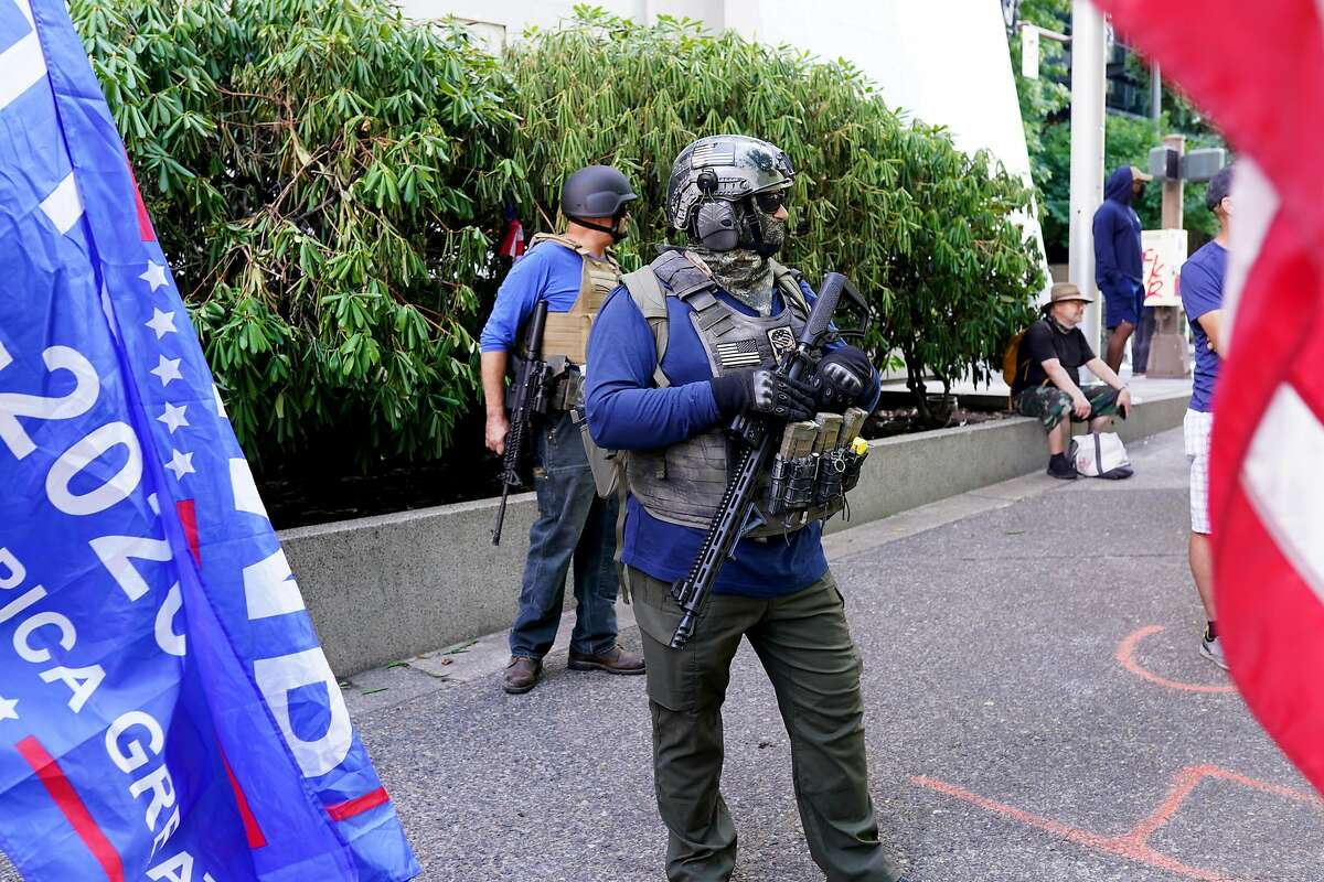 PORTLAND, OR - AUGUST 22: Right wing protesters with assault rifles look on during a rally in front of the Multnomah County Justice Center that drew anti-police counter protesters on August 22, 2020 in Portland, Oregon. For the second Saturday in a row, right wing groups gathered in downtown Portland, sparking counter protests and violence. (Photo by Nathan Howard/Getty Images)