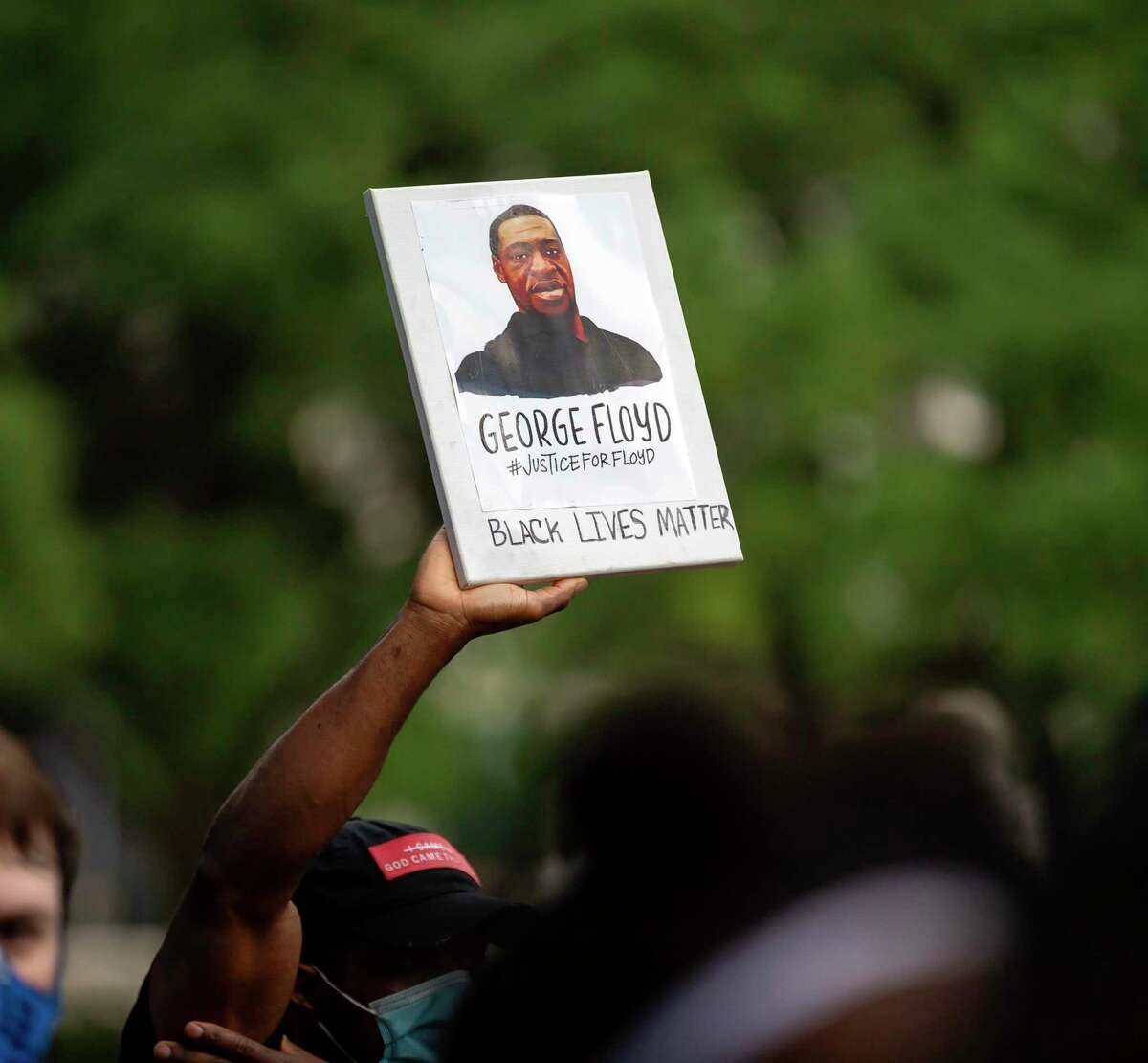 A demonstrator holds a sign at Houston city hall during a candle light vigil in honor of George Floyd who's death sparked protests throughout the country, Thursday, June 4, 2020.