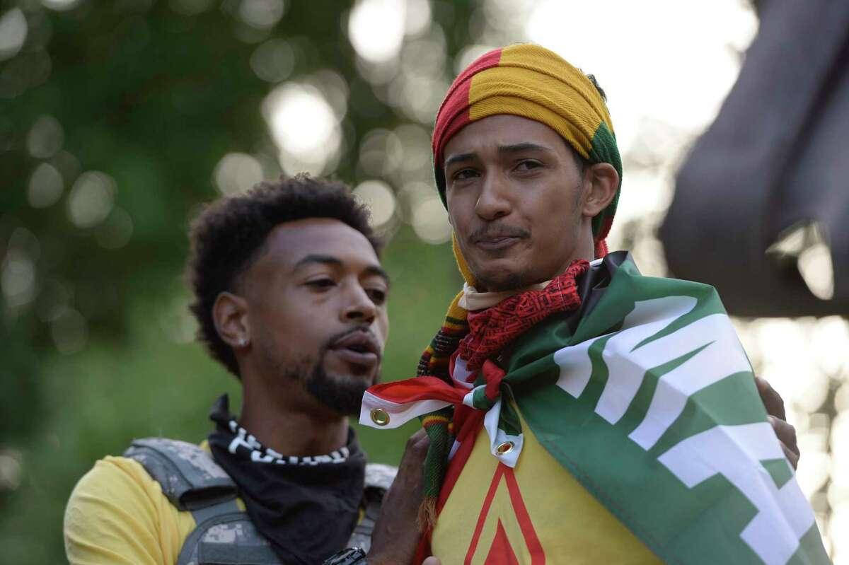 All Of Us organizer Lexis Figuereo, right, comforts Jermiah Hammond of Saratoga Springs at a rally and vigil Monday, Aug. 31, 2020, to mark the seventh anniversary of the police foot chase that led to the death of 21-year-old Darryl Mount in Saratoga Springs, N.Y. (Jenn March, Special to the Times Union)