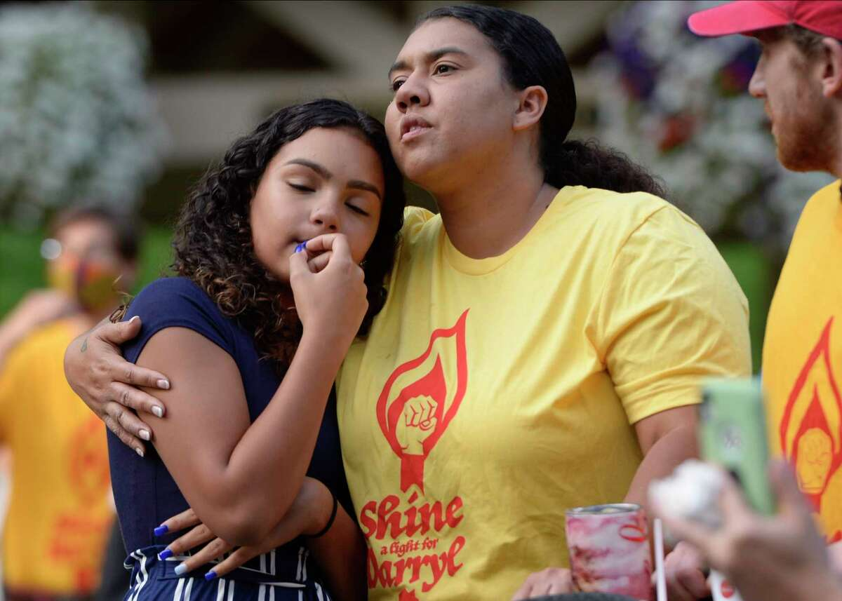 Spectators comfort each other as they listen to Jermiah Hammond (not shown) speak at a rally and vigil Monday, Aug. 31, 2020, to mark the seventh anniversary of the death of 21-year-old Darryl Mount in Saratoga Springs, N.Y. (Jenn March, Special to the Times Union)