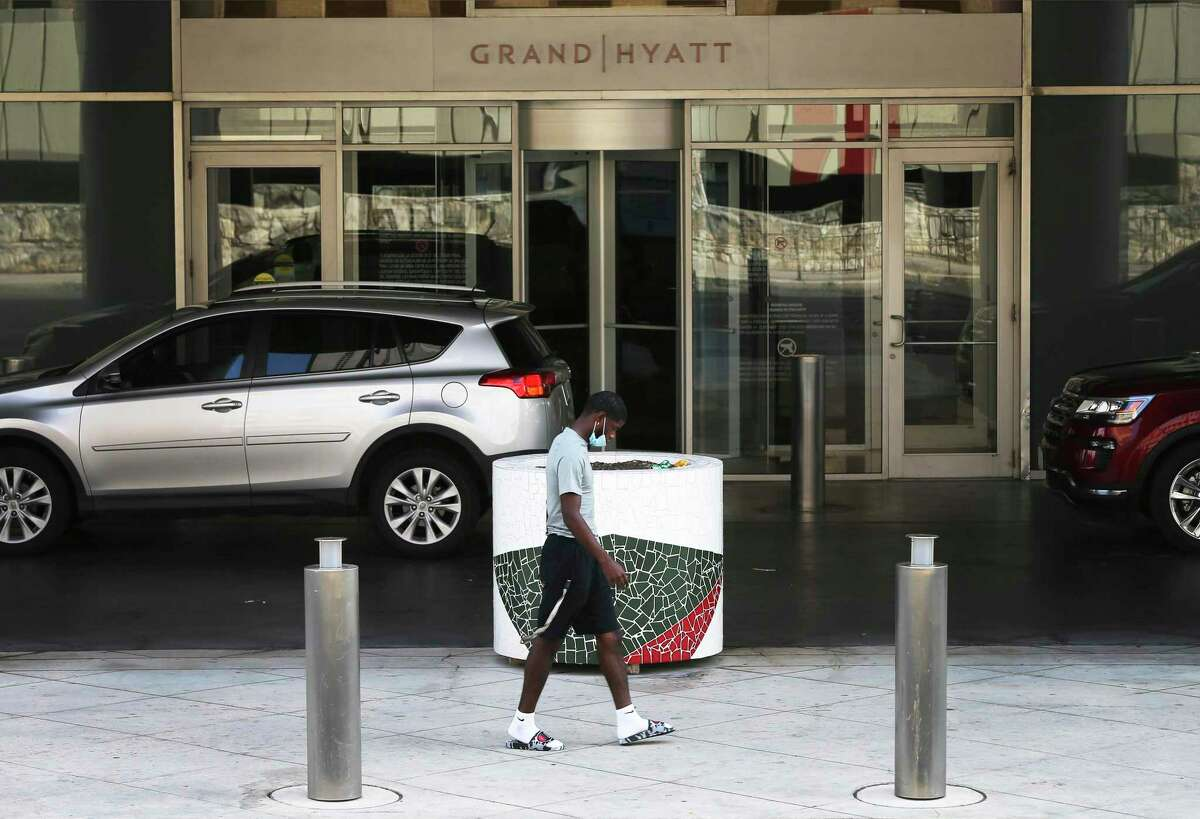 A man walks past the Grand Hyatt entrance on Monday, Aug. 31, 2020. The coronavirus pandemic slashed revenue for the Texas hotel industry by nearly two-thirds, according to a report.