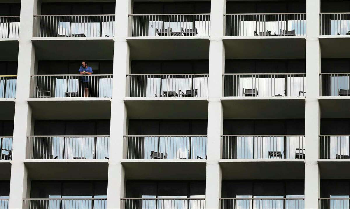 A man takes in a view of downtown on a balcony at Marriott Riverwalk hotel on Monday, Aug. 31, 2020. The coronavirus pandemic slashed revenue for the Texas hotel industry by nearly two-thirds, according to a report released Monday. The state's hotels took in $1.175 billion in the quarter ending June 30, a 64.1 percent decline from a year earlier, according to the report from Source Strategies, which tracks hotel occupancy and revenue.